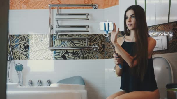 Brunette girl sitting on toilet in bathroom hold smartphone in blue monopod.