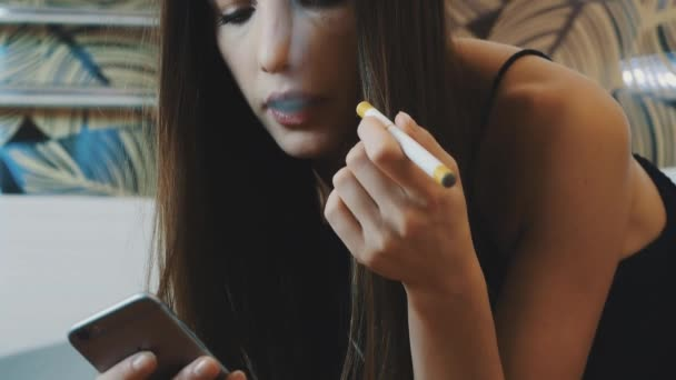 Portrait of young girl sit on toilet with phone and smoke electronic cigarette.