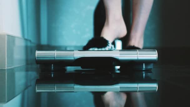 Žena, odkládal pantofle vstát na moderní váhy v bytě. Vážení