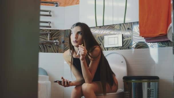 Girl sitting on toilet holding phone. Smoking electronic cigarette. Steam