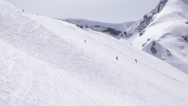 Lyžařské středisko. Snowboardisté jezdí na svahu. Lyžaři. Bílá hora. Slunečný den. Rychlost