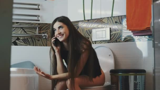 Brunette girl sitting on toilet emotionally talking on phone. Bathroom. Laugh
