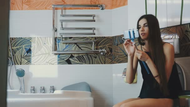 Brunette girl sit on toilet in bathroom hold smartphone in blue monopod.
