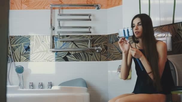 Brunette girl sit on toilet in bathroom hold smartphone in blue monopod.