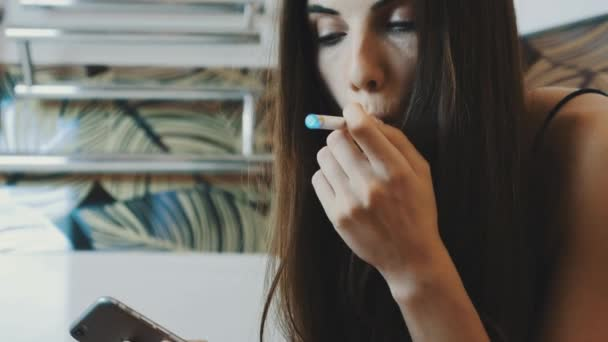 Young girl sitting in bathroom with smartphone. Smoking electronic cigarette.