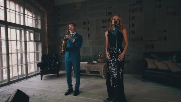 Zpěvák v zářících šatech provádí na jevišti saxofonista. Retro styl. Jazz