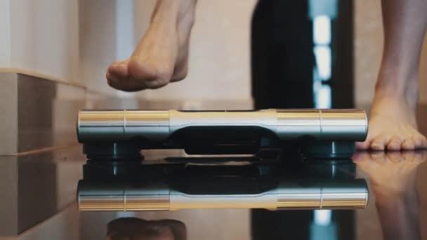Žena postav se na zářící moderní váhy v bytě. Bosé nohy. Vážení