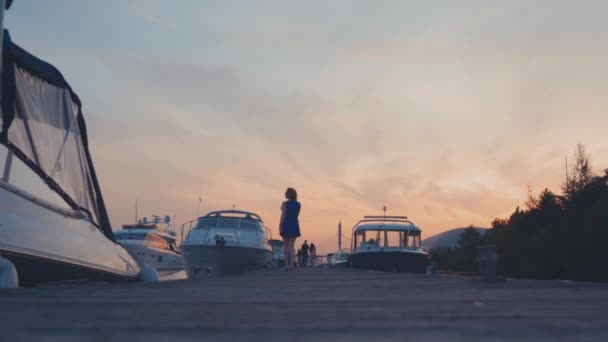 Young girl in blue dress run on wooden pier at coast on sunset. White yachts