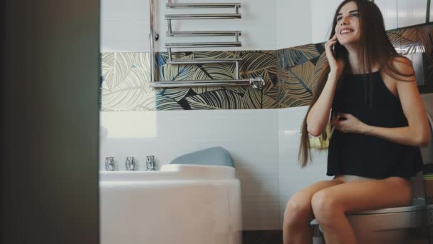 Brunette girl sit on toilet talk on phone. Smoking electronic cigarette. Laugh