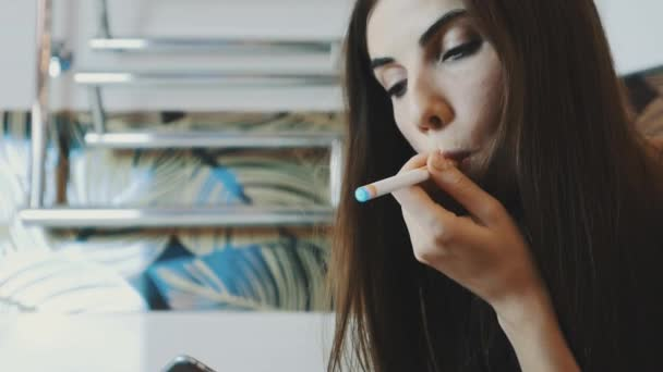 Young girl sitting in bathroom using smartphone. Smoking electronic cigarette.