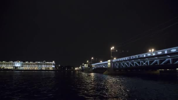View of bridge above river in night in city. Lights. Tourist boats. Timelapse.