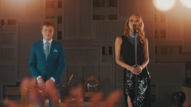 Jazz-Sänger in leuchtende Kleid und Saxophonist im blauen Anzug auf ...