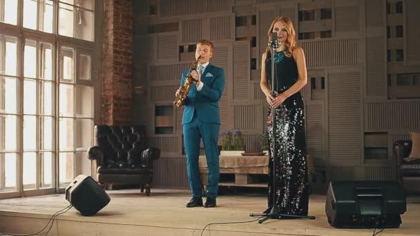Jazz-Sänger in Blendung Kleid und Saxophonist im Anzug Perfrorm auf ...