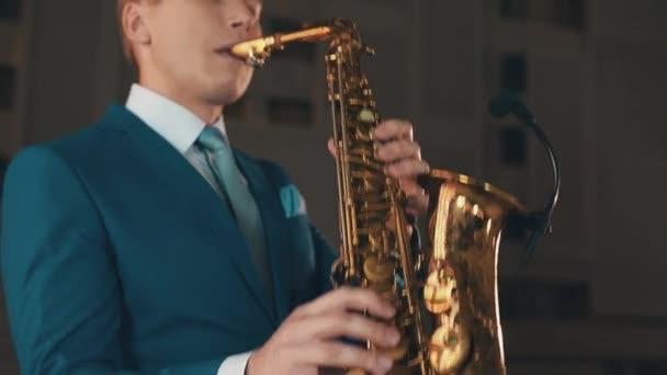 Saxofonista v modrém obleku hrát jazz na zlatý saxofon ve fázi. Hudba. Umělec