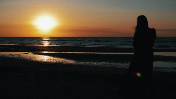 Silhouette of girl posing to photographer on beach on sunset. Sea. Photoshoot.