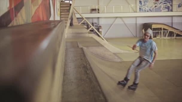 KRASNOYARSK, RUSSIA - MARCH 15, 2014: Roller skater in glasses slide on edge of springboard in skatepark. Challenge. Audience. Contest