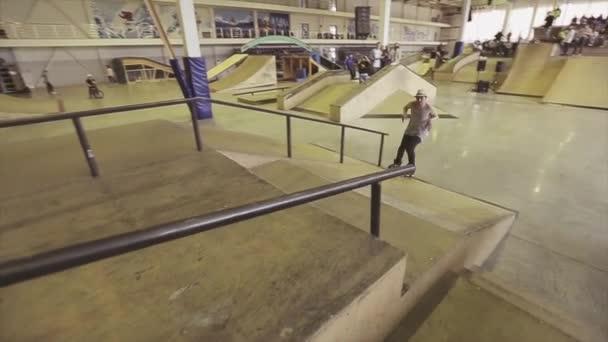 KRASNOYARSK, RUSSIA - MARCH 15, 2014: Roller skater in hat make extreme jump on edge of springboard in skatepark. Challenge. Competition