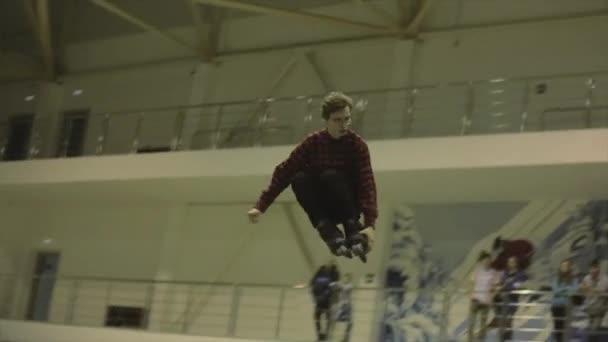 KRASNOYARSK, RUSSIA - MARCH 15, 2014: Roller skater grab feet in jump, 180 flip. Springboard. Extreme stunt. Competition in skatepark.