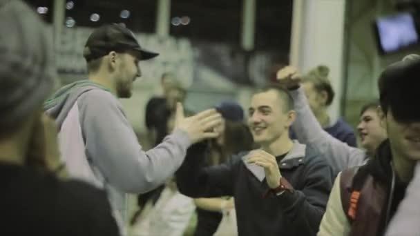 Krasnojarsk, Rusko - 15. březen 2014: bruslari skok, úsměv na jevišti na hospodářskou soutěž ve skateparku. Lidé tleskají. Vítězové