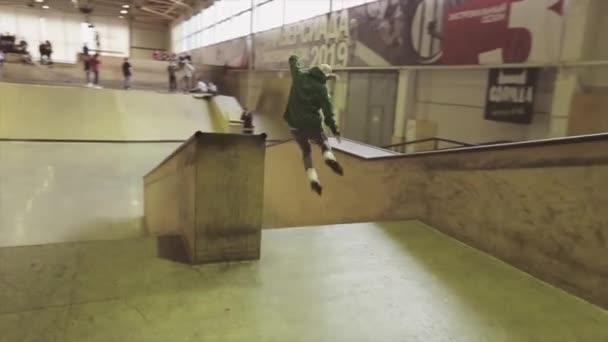KRASNOYARSK, RUSSIA - MARCH 15, 2014: Roller skater in green hoody make jump, grab feet in air. Extreme hobby. Competition in skatepark