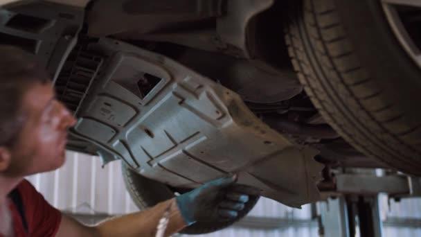 Auto mechanik opravuje auto na výtahu v čerpací stanici
