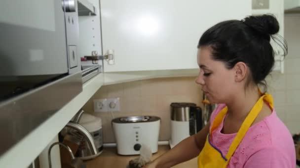 Krásná žena myje nádobí v dřezu