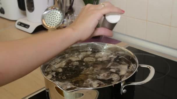 Žena soli houbová polévka v rendlíku