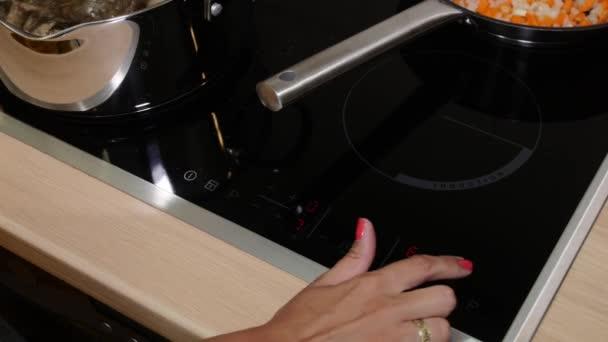 Žena stiskne tlačítko na sporák