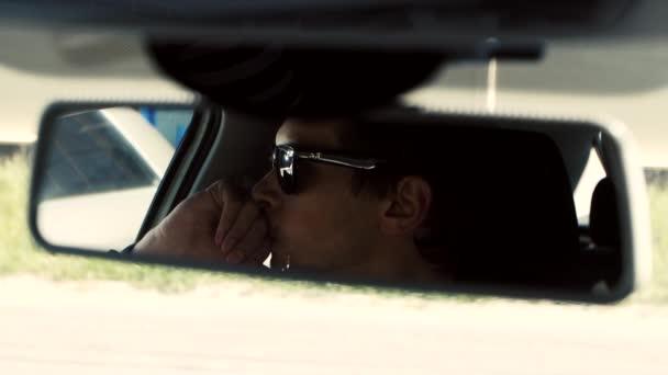 Člověk sedí v autě. Odraz tváře v zrcátku automobilu