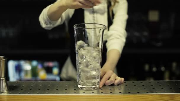 Barkeeper vermischt das Eis in einem Glas