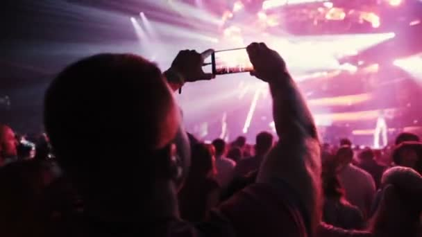 MOSCOW, RUSSIA - AUGUST 15, 2015: 20 years of Radio Record. Man shoots concert with mobile phone. Slow motion