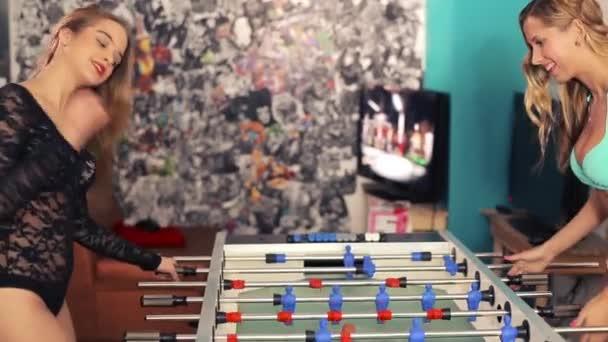 Dvě ženy, lesby v prádle, hrát stolní fotbal