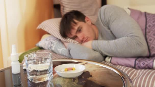 Kranker Mann nimmt Tablette im Bett.