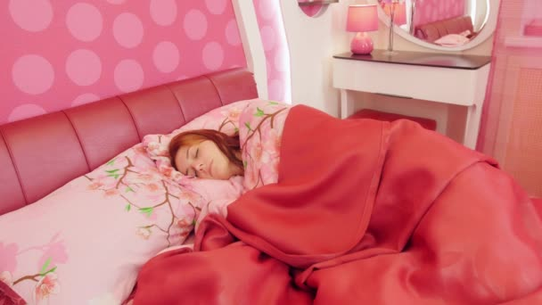 Woman sleeping in pink bed. Tossing and turning