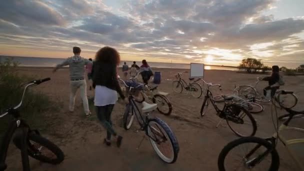Group of people leave their bicycles on a sand beach and run to  water in sunset