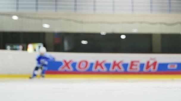 Hokejista v modré zařízení zaměření se na brzdy před kamerou. Ledový sprej