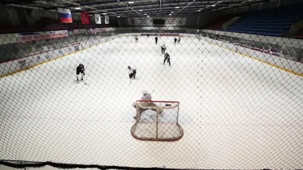Zadní strana hokejový brankář v okamžiku hry na kluzišti. Zpomalený pohyb.