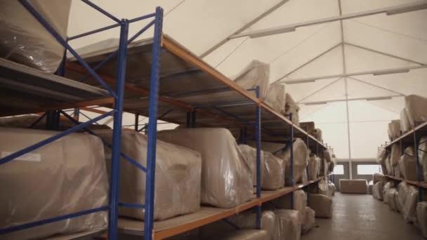 Velké tašky v kartonu leží na dřevěné regály do skladu. Pan vodorovně