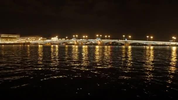 Pohled na most a řeku v noci city. Motorový člun plave řece
