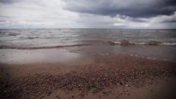 Malé mořské vlny na pláži s kamínky. Šedý mrak nebe. V létě. Pan jezdec