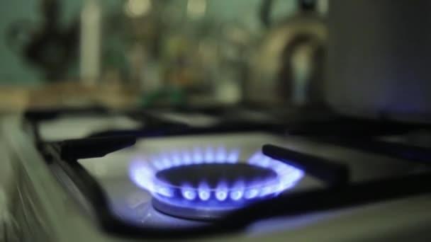 Kladení obrovského hliníkového hrnce na hořící plynový sporák. Modrý oheň