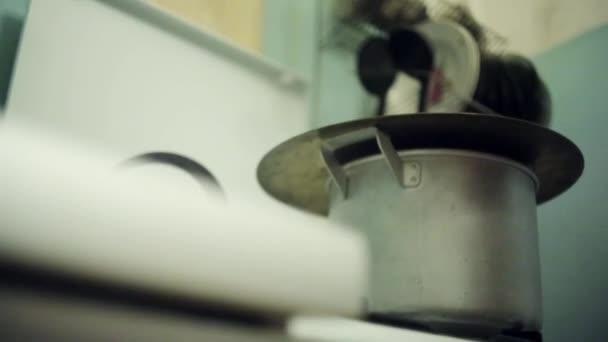 Muž ruku odkrýt pánev na plynový sporák staré kolo buben destičku. Dům umění