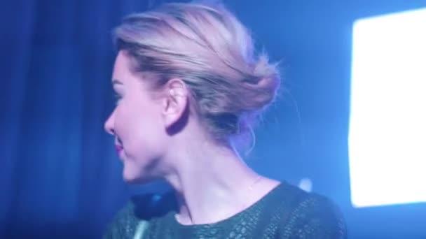 attraktives DJ-Mädchen in schwarzem Top mixt, lächelt, singt am Plattenteller im Nachtclub