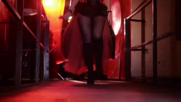 Frauenbeine in Stiefeln auf Stöckelschuhen gehen aus dem Cutrain und beschmutzen den roten Teppich