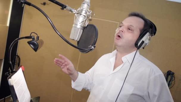 Man sing in headphones in front of microphone. Hand gesticulation. Studio