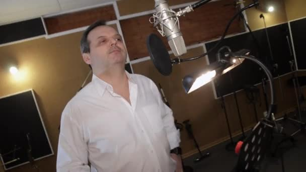 Adult man in white shirt sing in studio in front of microphone. Hand play