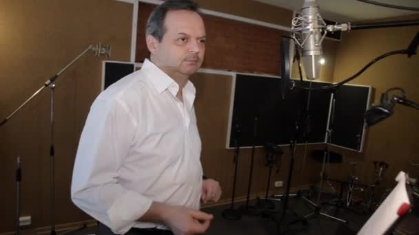 Adult man in white shirt sing in studio in front of microphone. Clicking fingers