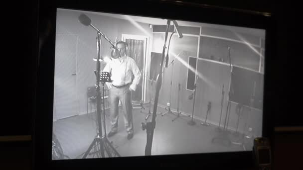 Photo Man in shirt sing in studio in front of microphone. Surveillance camera view
