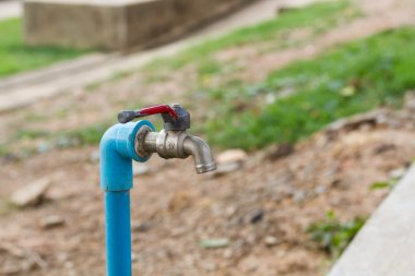 Blue tube and old faucet in the garden