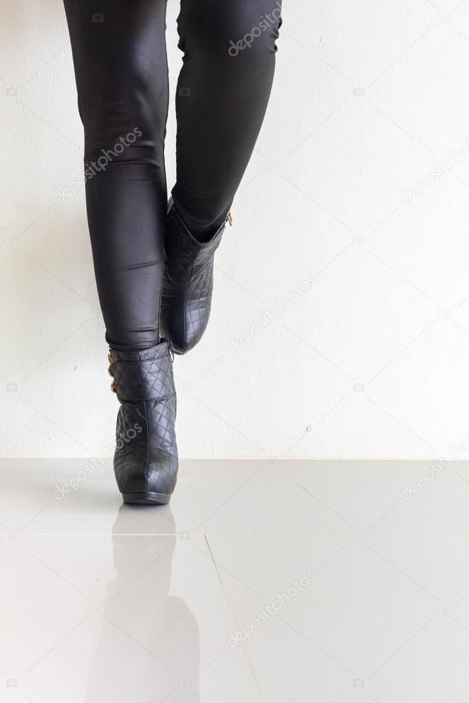 ce8a6e43574a Kvinna som bär svart läder byxor och höga klackskor — Stockfotografi ...